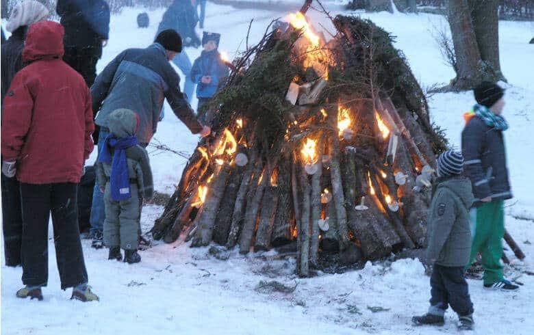 Menschen schauen auf das Osterfeuer