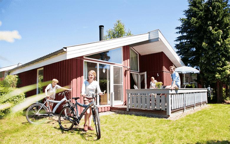 Zwei Kinder mit Fahrrädern vor dem Haus. Beide Eltern auf der Terrasse vom Ferienhaus.