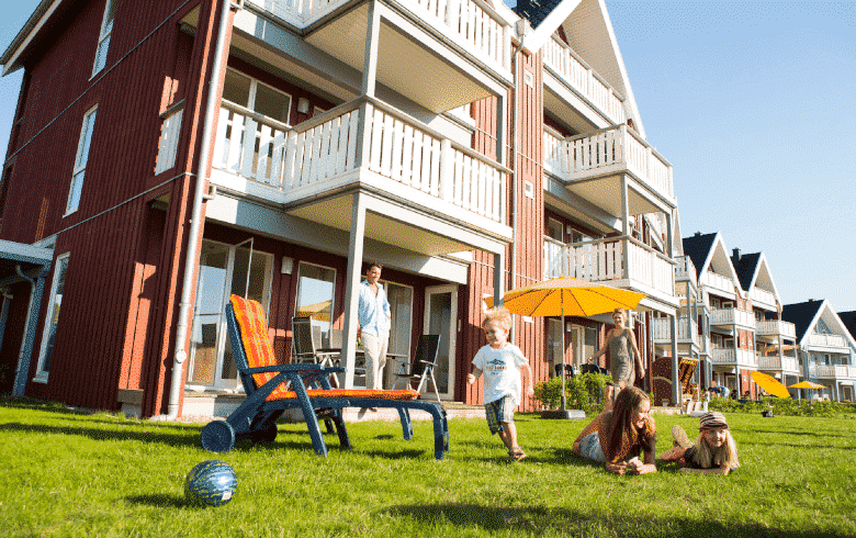 Eine Familie vor einer Ferienwohnung. Kinder spielen auf der Rasenfläche